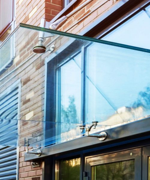 Transparent,Glass,Awning,Over,Front,Door,Of,Multistory,Brick,Apartment